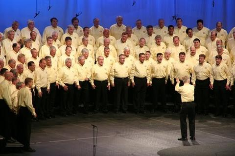 A cropped photo of a harmony brigade chorus all in yellow shirts and black slacks.